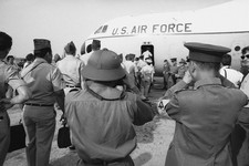 -                In this March 27, 1973 photo, Viet Cong and North Vietnamese members of the joint military commission, foreground, shoot photos of U.S. troops as they board an Air Force plane for the f