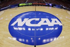 -                FILE - In this March 21, 2013, file photo, in this image taken with a fisheye lens, the NCAA logo is displayed at mid-court before Albany's practice for a second-round game of the NCAA