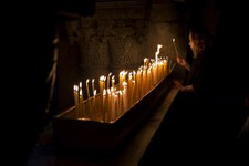 -                A Christian Catholic pilgrim lights a candle inside the Church of the Holy Sepulcher, traditionally believed to be the site of the crucifixion of Christ, in Jerusalem's Old City, Friday