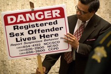 -                File - In This May 18, 2001 file photo, Nueces County Texas District Attorney Carlos Valdez looks at one of the signs that District Judge Manuel Banales ordered 21 registered sex offend