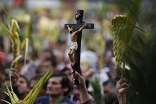 -                Faithful hold palm fronds and a crucifix during a Palm Sunday Mass at the Baby Jesus Church in Bogota, Colombia, Sunday March 24, 2013. According to the New Testament, Palm Sunday marks