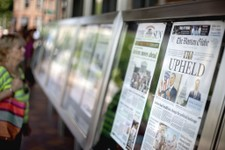 -                FILE – In this June 29, 2012 file photo front pages of the days' newspaper front pages are displayed at the Newseum in Washington, after the previous day's Supreme Court ruling to uphol