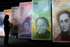 -                FILE - In this Oct. 24, 2007 file photo, a woman looks at oversized versions of the new Venezuelan currency, coined the 'Strong Bolivar' in Caracas, Venezuela. Thousands of companies su