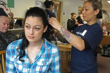 -                In this photo taken March 30, 2013, in Sitka, Alaska, volunteer hair stylist Khit Sypakanphay of Anchorage, Alaska, right, fixes the hair of Mount Edgecumbe High School student Kaitlyn