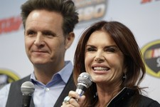 -                Mark Burnett, left, and Roma Downey talk to the media prior to the start of the STP 500 Sprint Cup series auto race at Martinsville Speedway in Martinsville, Va., Sunday, April 7, 2013.