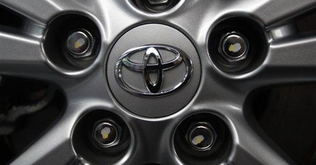 Toyota ekes out quarterly profit, raises forecast