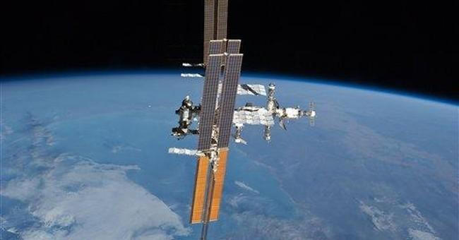 Spacewalking astronauts release mini-satellite