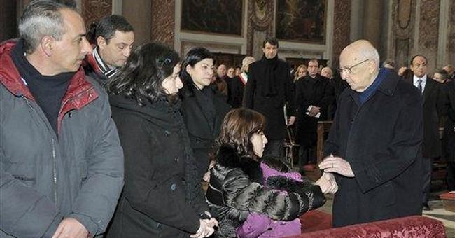 Relatives toss roses into sea near Italian ship