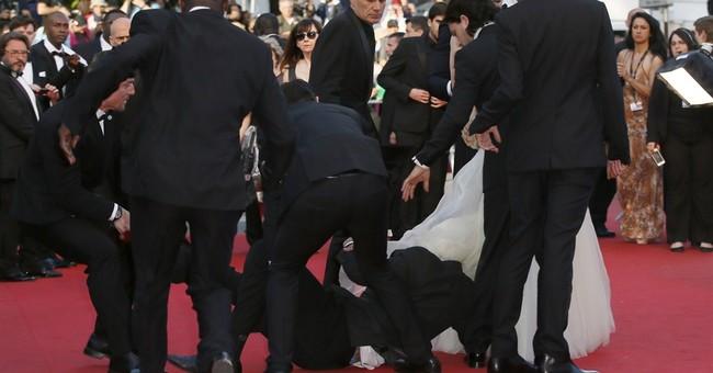 Man dives under star's dress on Cannes red carpet