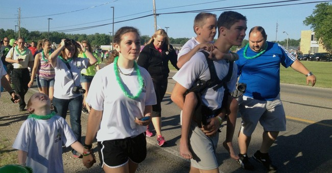 Michigan teen begins 40-mile trek carrying brother