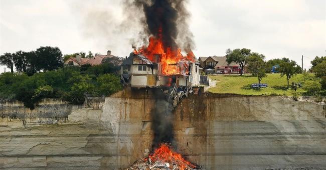 Fire crews burn house teetering on Texas cliff