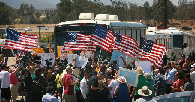 Buses with migrant families rerouted amid protest
