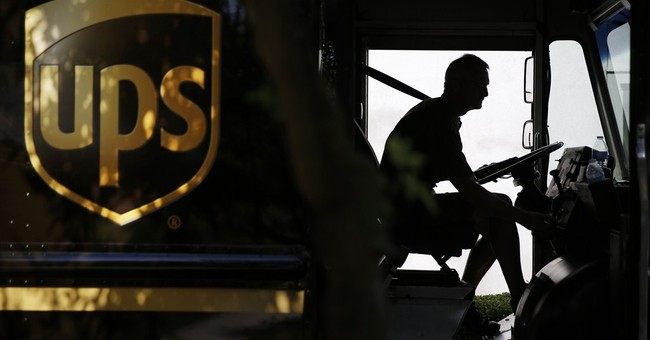 UPS 2Q profit drops, lowers outlook on spending