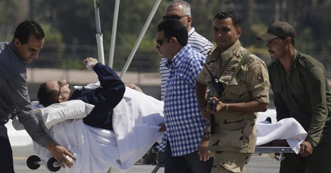 Egypt's Mubarak defends his rule in courtroom cage