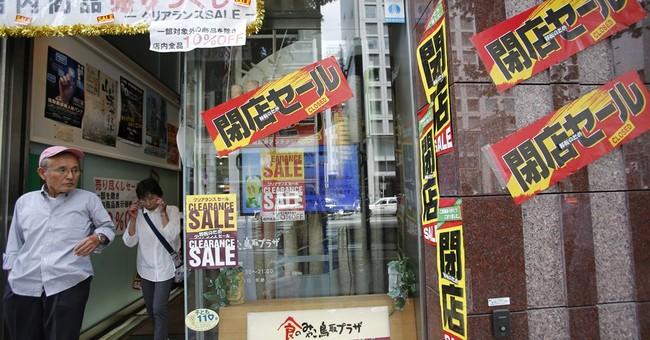 Japan's economy shrinks as tax hike hits spending