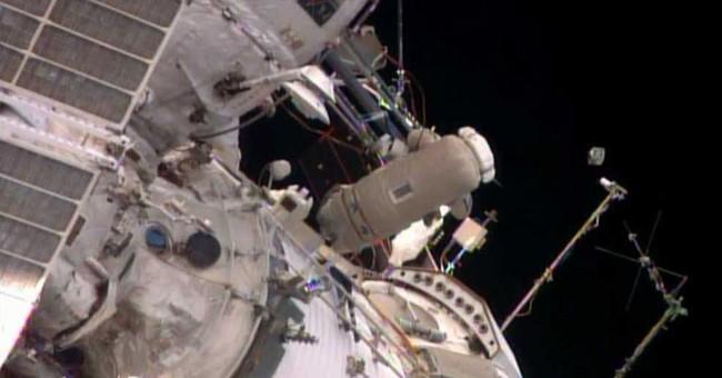 Spacewalking astronauts release baby satellite