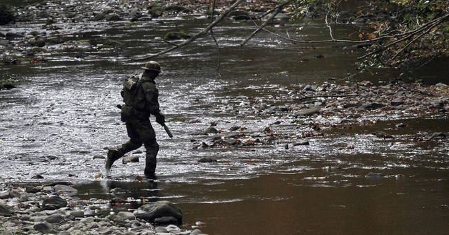 Police on manhunt find pipe bombs in woods