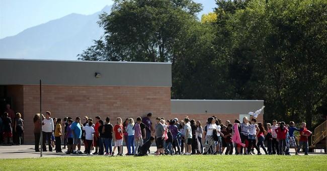 Teacher whose gun fired in school bathroom charged
