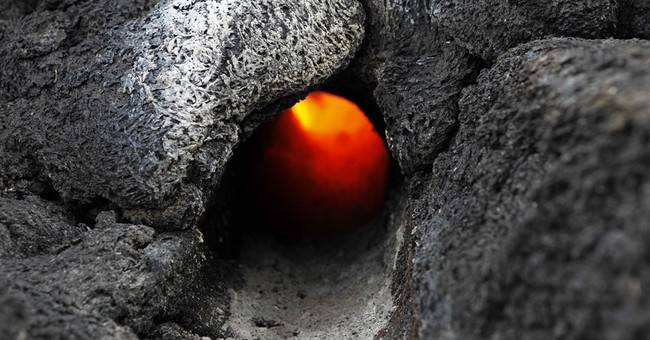 Lava flow steams through lush forests in Hawaii