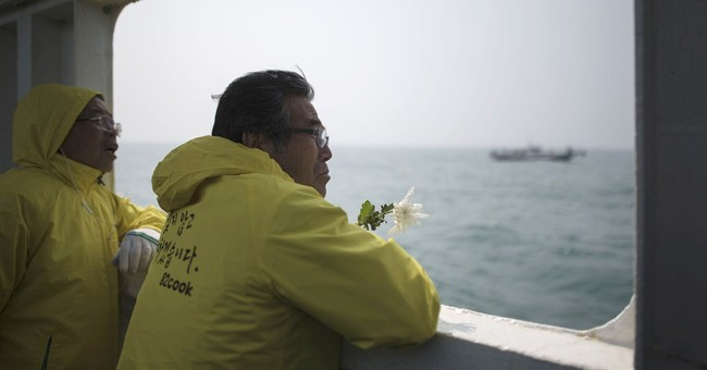 AP PHOTOS: Relatives weep, toss flowers for ferry dead