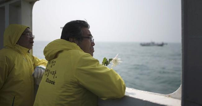 AP PHOTOS: Relatives weep, toss flowers for ferry dead