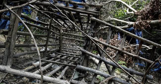 Malaysian forensics teams dig up graves at traffickers' camp
