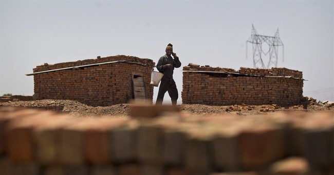 Image of Asia: Working at a brick kiln in the summer heat