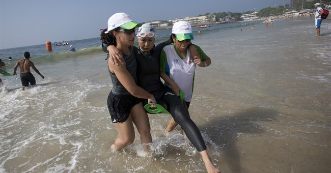 Triathletes shrug off water warnings, swim in Rio