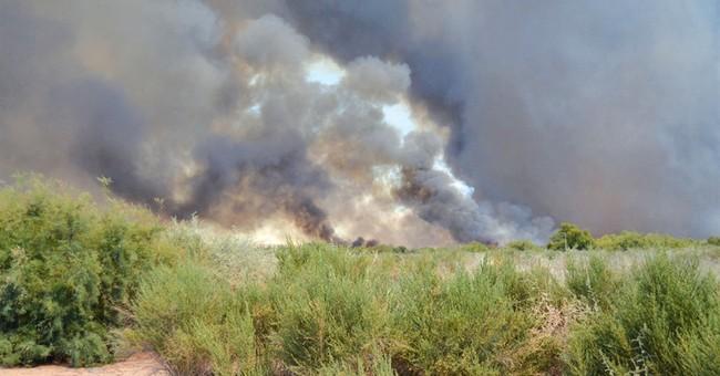 Wildfire burning near massive blaze expands
