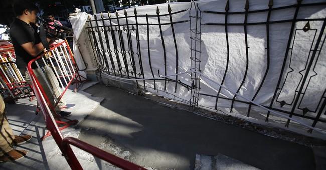 The Latest on Bangkok: Thai police issue arrest warrant