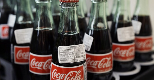 Coke's profit hit by strong dollar, repositioning