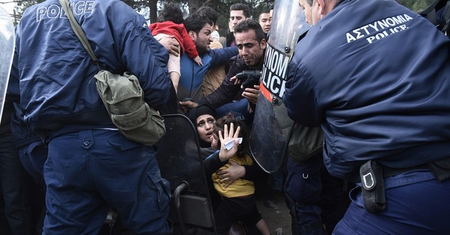 Migrants barred from crossing into Macedonia hold protest