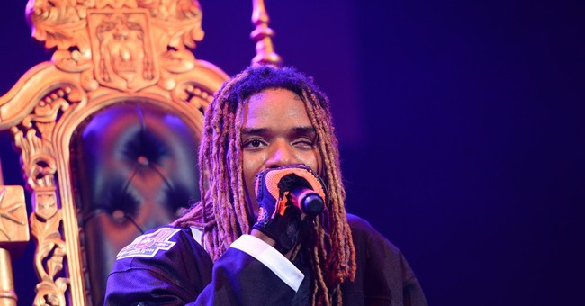 Fetty Wap throws wads of money over balcony to fans at mall