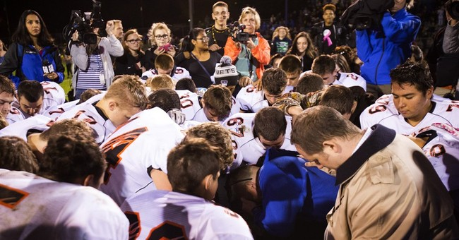 Washington coach suspended for praying files complaint