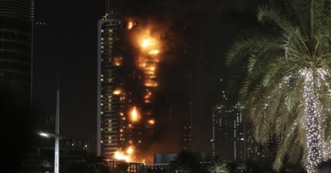 Dubai New Year fireworks kick off while nearby tower blazes