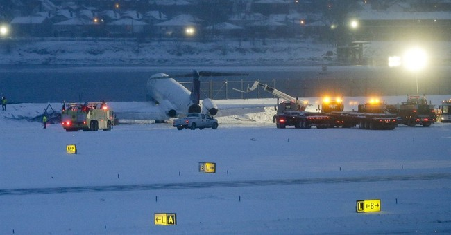 Plane skids off snowy New York runway, stops next to icy bay