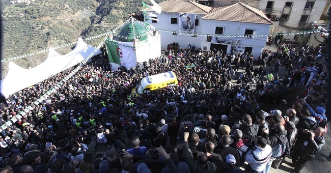 Algerian hero and longtime opposition leader buried in chaos