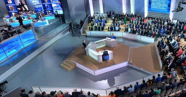 Putin seeks to charm, insists Russian economy on the mend