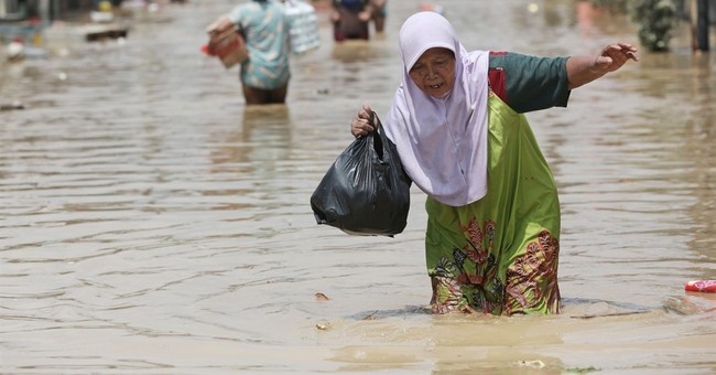 Image of Asia: Trying to walk on a flooded Indonesian street