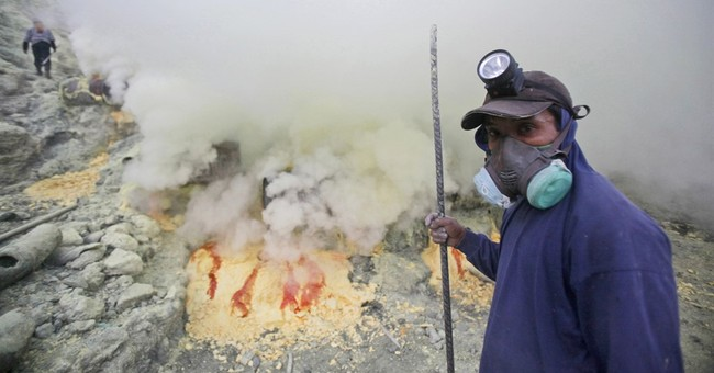 Indonesian sulfur miners brave volcano, fumes, earn pennies
