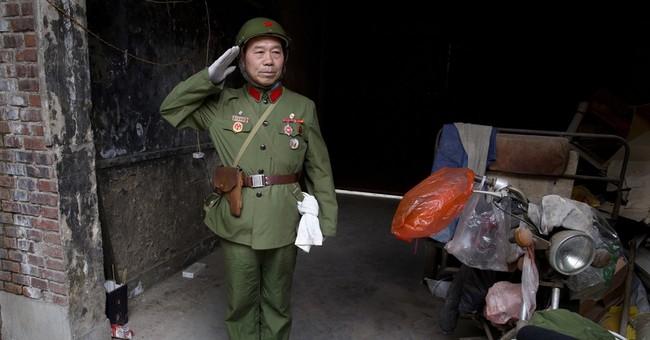 Garbage picker in military attire sings Mao's praises