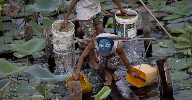 As lines form for water, Myanmar pins hopes on Suu Kyi