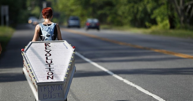 Woman towing casket finishes walk highlighting mental health