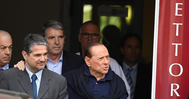 Berlusconi leaves hospital weak, hopes to still help Italy