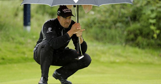Mickelson shines in wind and rain, keeps British Open lead