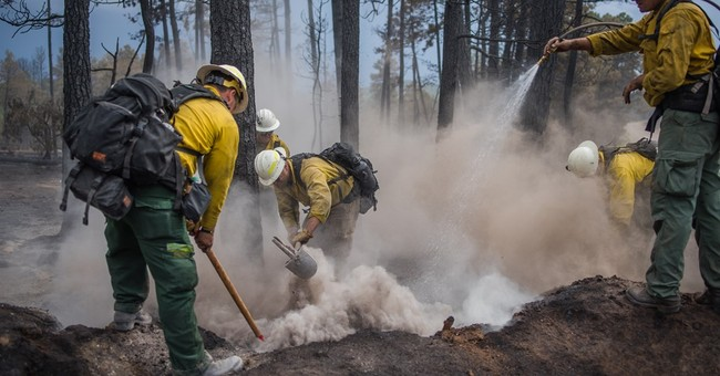 Crews work to keep blaze from highway near the Grand Canyon