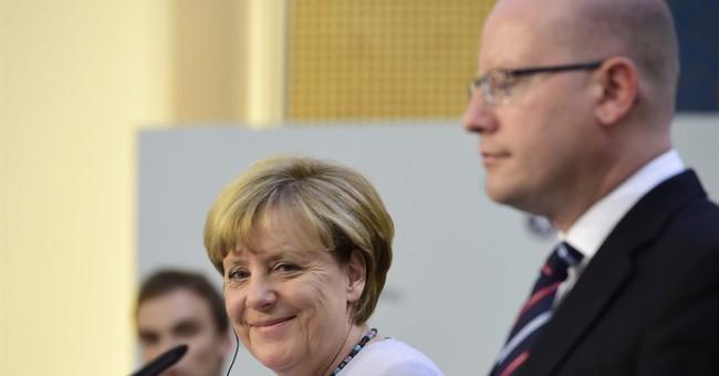 Merkel rejects Muslim migrant ban, urges fair distribution