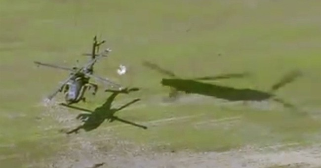 Military helicopter rescues stuck chopper from muddy field