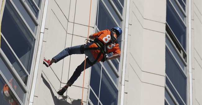 Colorado governor rappels down Denver high-rise for charity