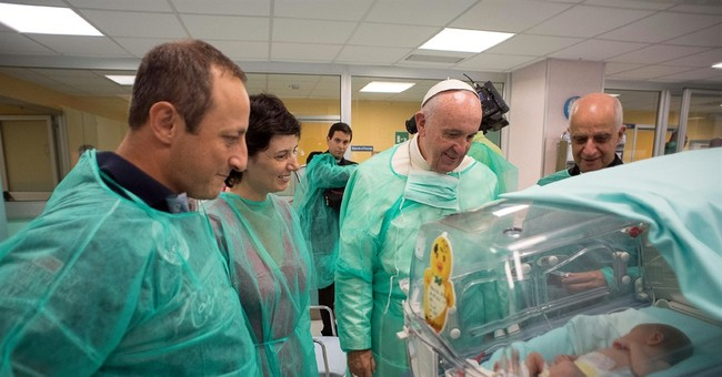 Pope dons scrubs to visit premature babies at Rome hospital